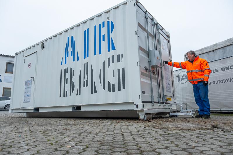 Der Mitarbeiter verläßt den Container.