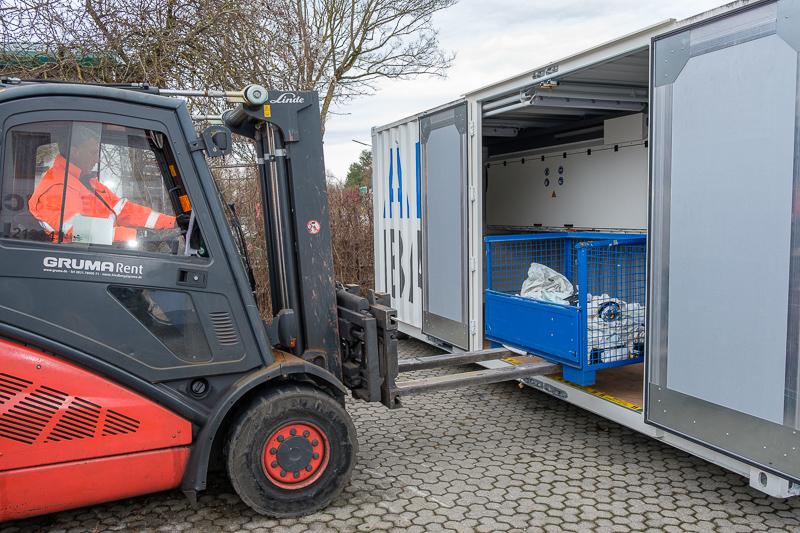 Ein Gabelstapler entnimmt dem Container eine Gitterbox mit gezündeten Airbags.